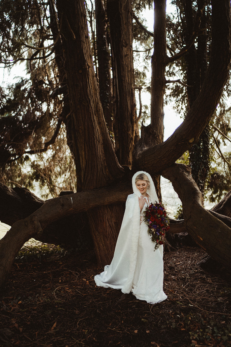 Bride in a white winters coat standing by a tree