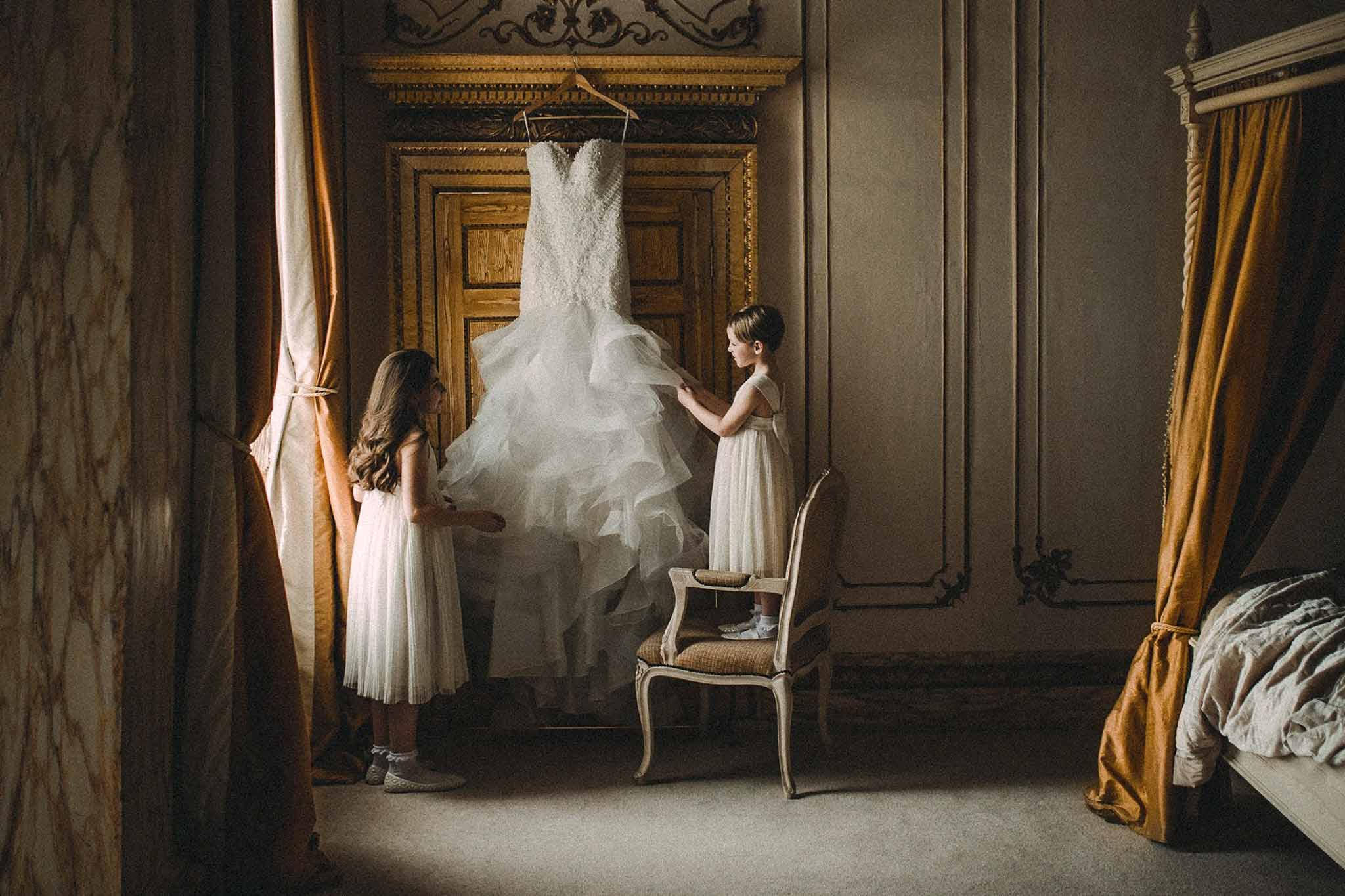 Two young children looking at the brides wedding dress