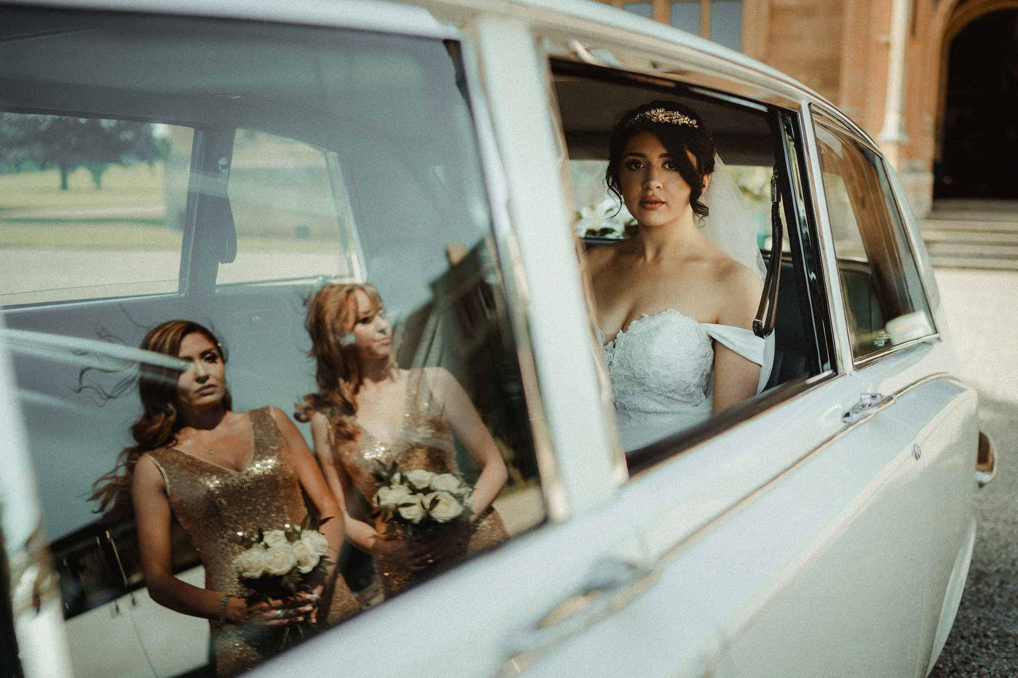 Bride in her wedding car, as the reflection of her bridesmaids are shown in the window| Fine art photography