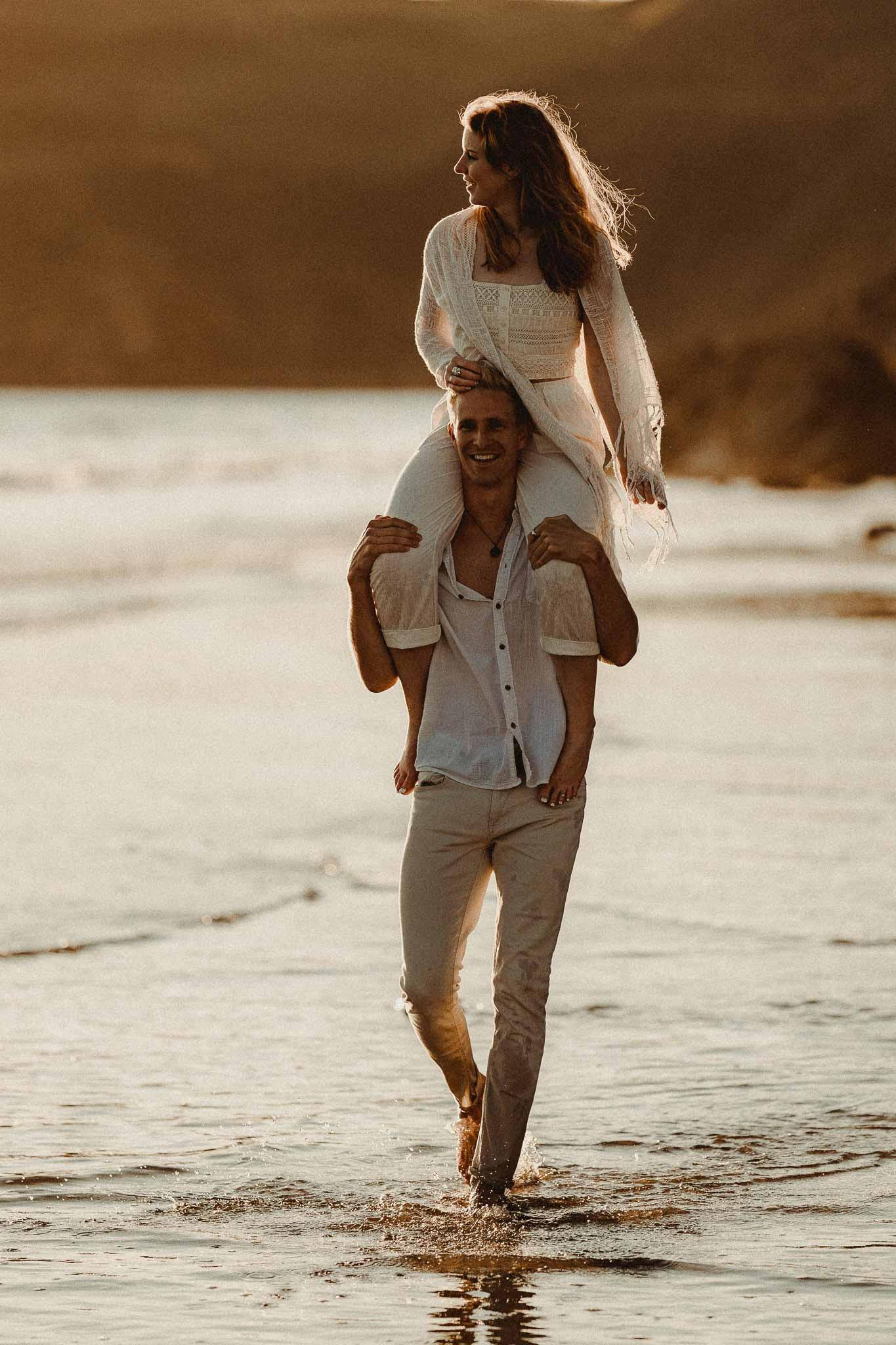 A man carries his partner on his shoulders across the beach