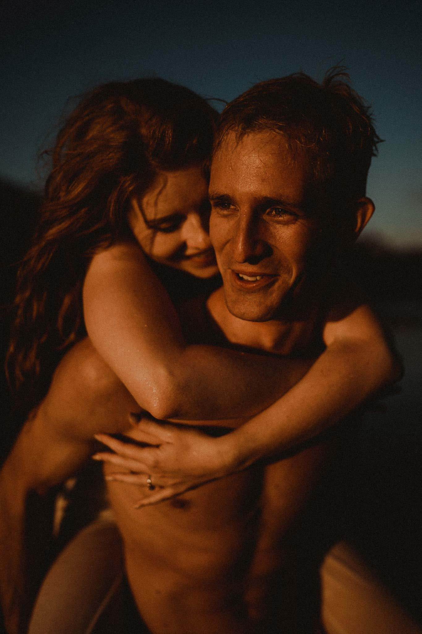 A Couple having a piggyback ride across the beach - full of smiles as sunset goes down