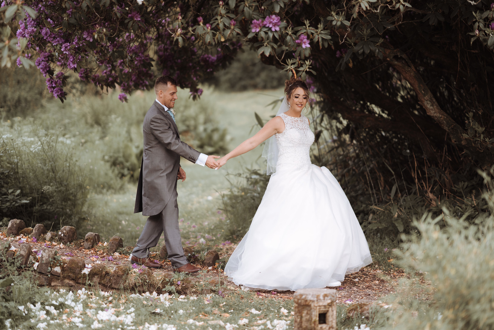 Bride and groom, hand in hand, walk through the greenery of the outside venue