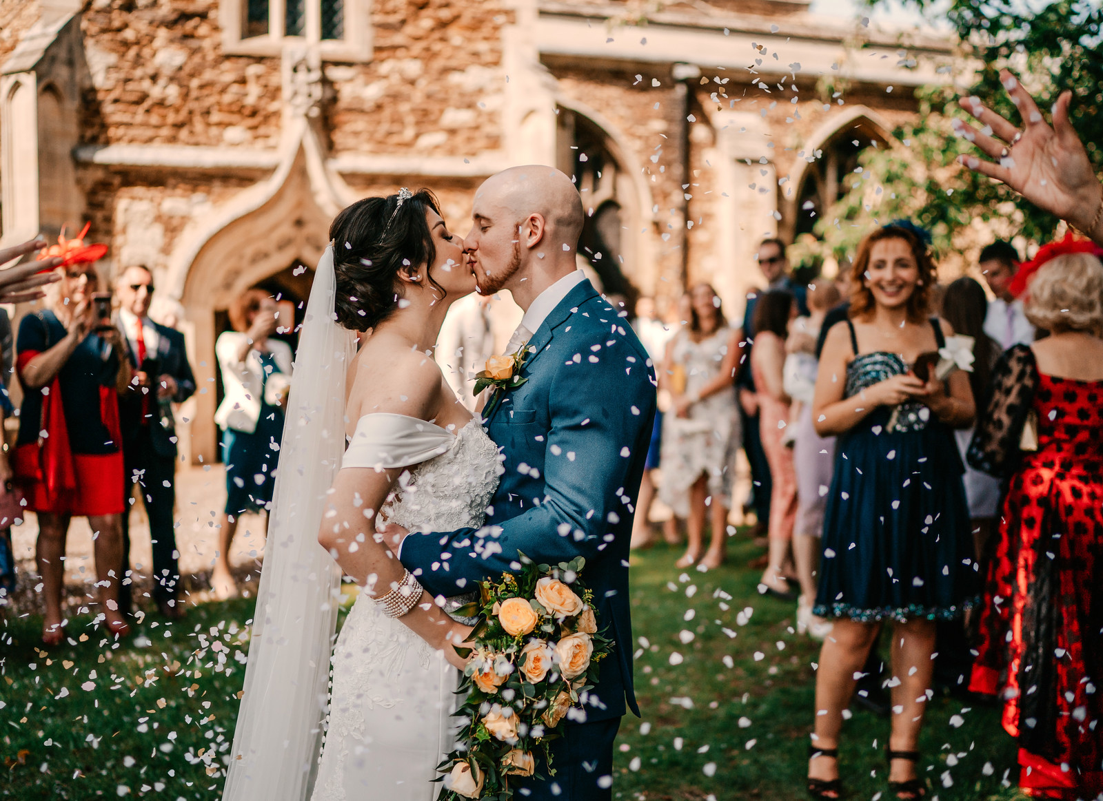Bride and groom kiss as family and friends throw confetti over the happy couple - Columbia Wedding Photographers