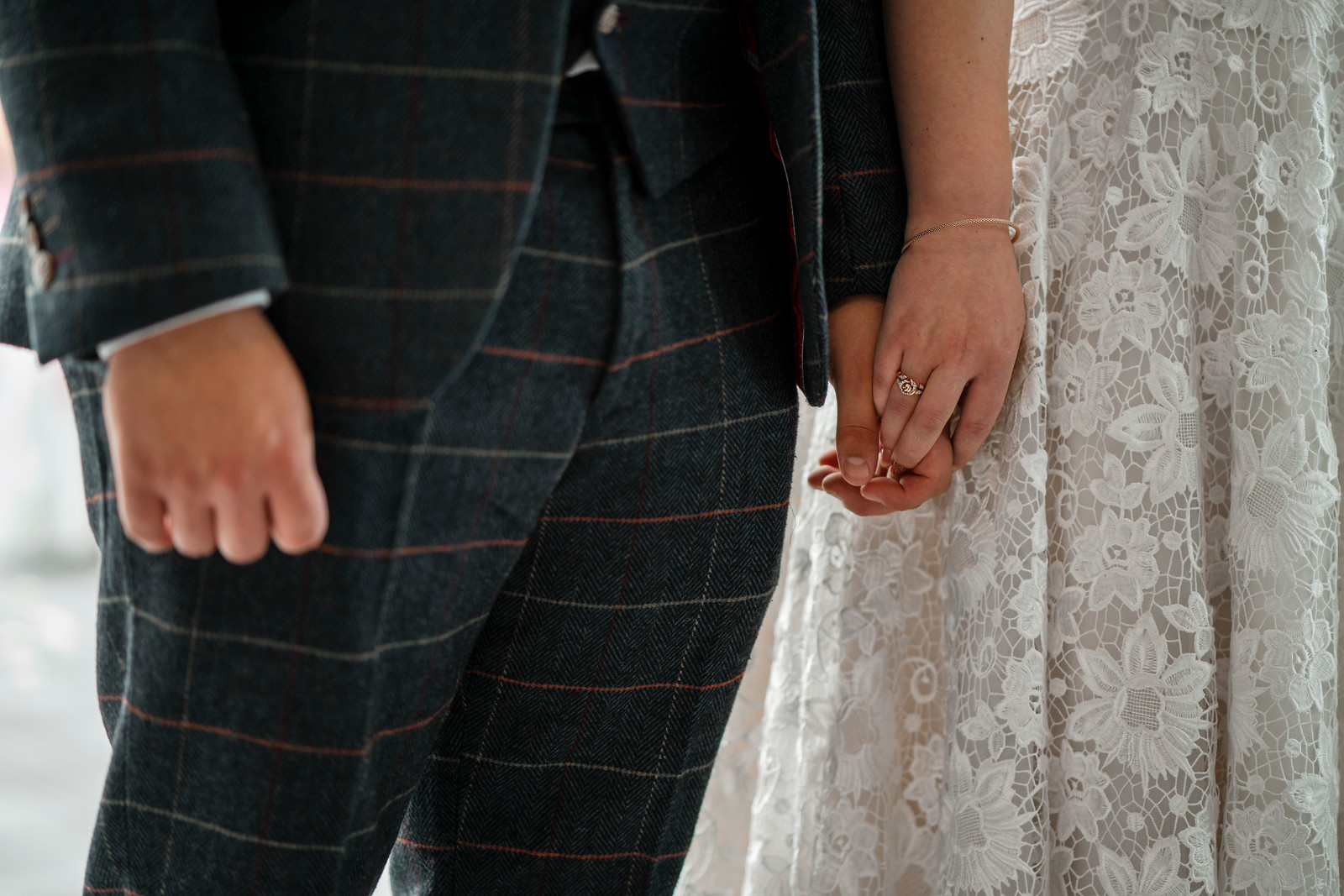 Close of bride and groom holding hands