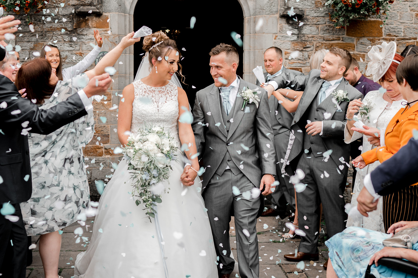 Bride and groom walk out of their venue as family and friends throw confetti over them