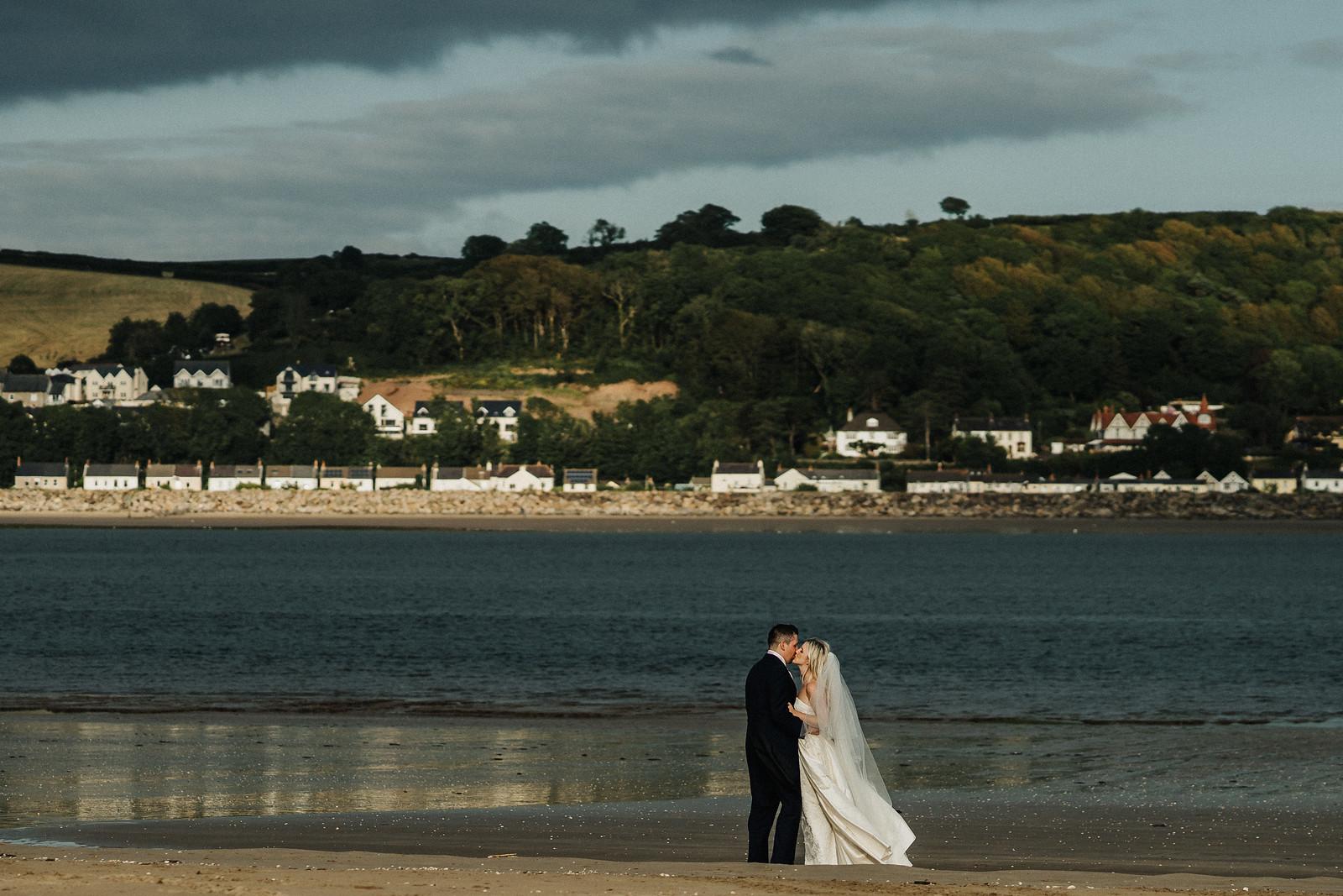 Stunning beach background, bride and groom kiss wedding photo