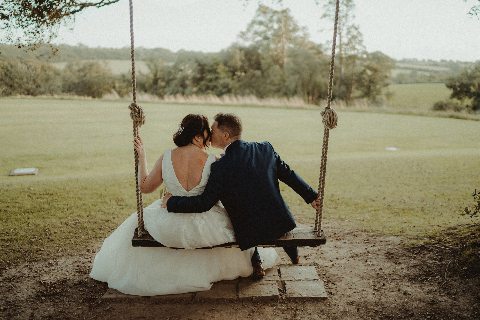 Bride and groom kiss as they are sat on the wedding swing