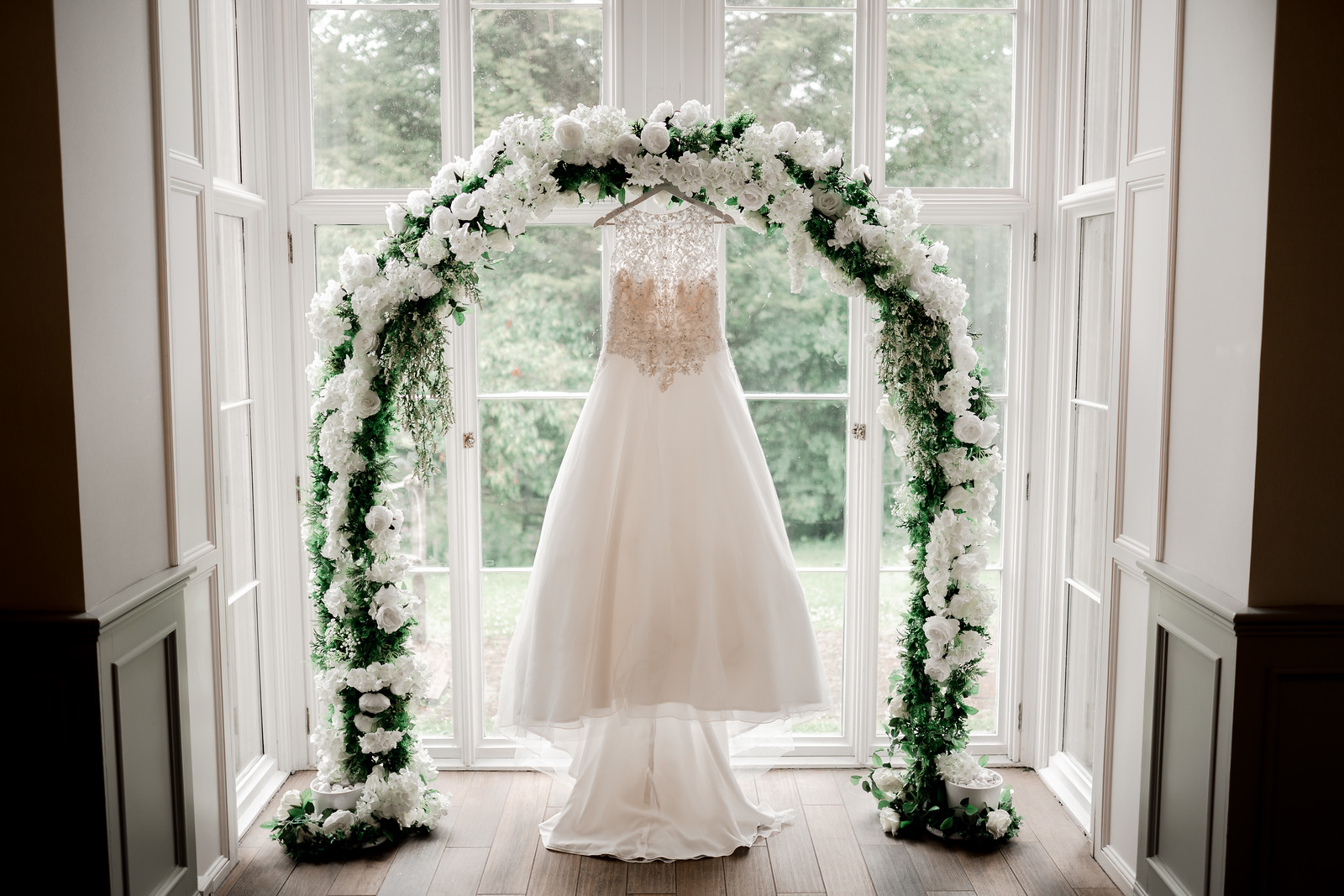 Brides wedding dress hung in the middle of an archway of flowers