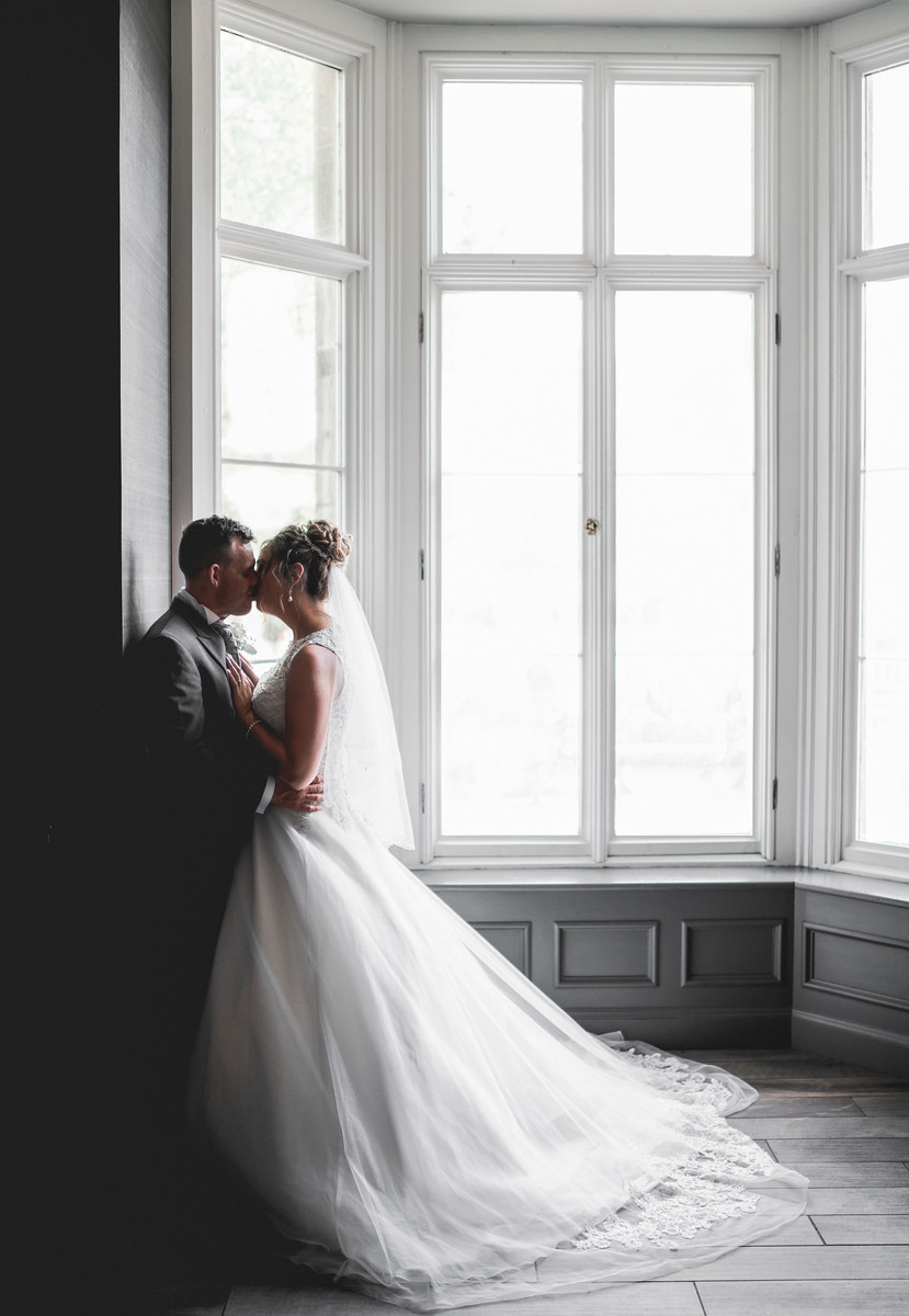Bride and groom kiss by a window in their wedding venue