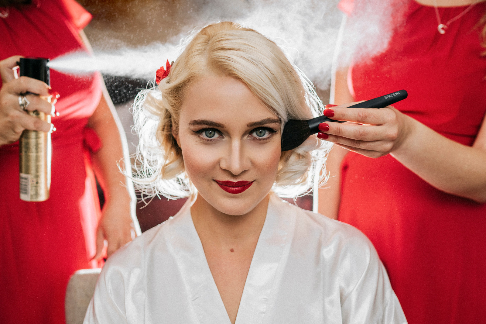 Beautiful wedding photo of bride as she gets her hair and make up done -