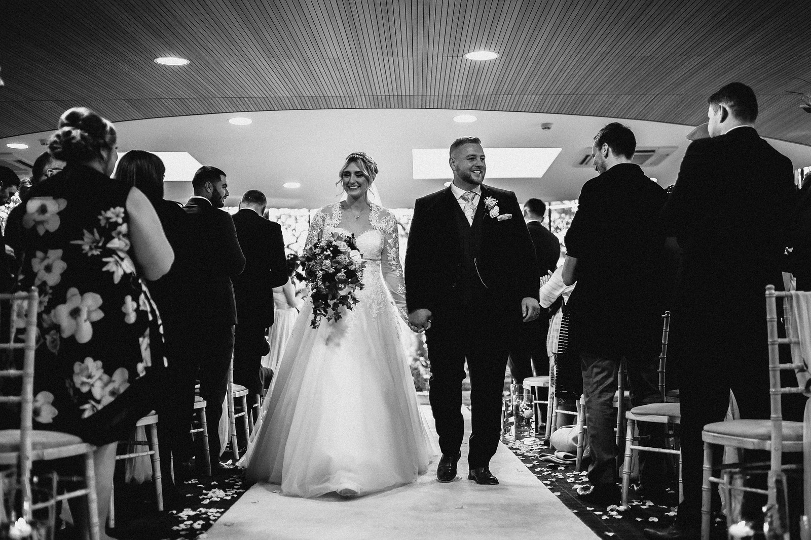 Bride and Groom full of smiles walk down the aisle together
