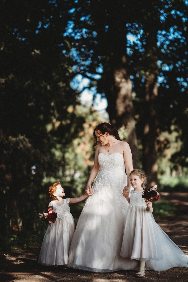 Brides and her two daughters walk through the beauty surrounding the venue