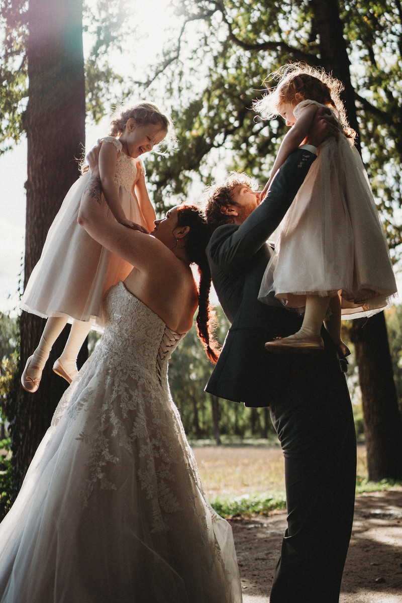 Bride and groom hold their daughters into the air as they are laughing