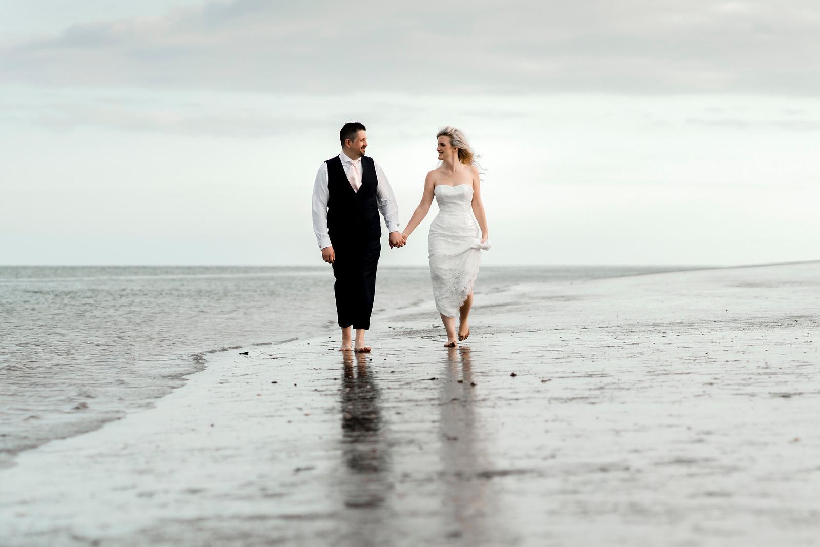 Bride and groom walk across the beach, hand in hand