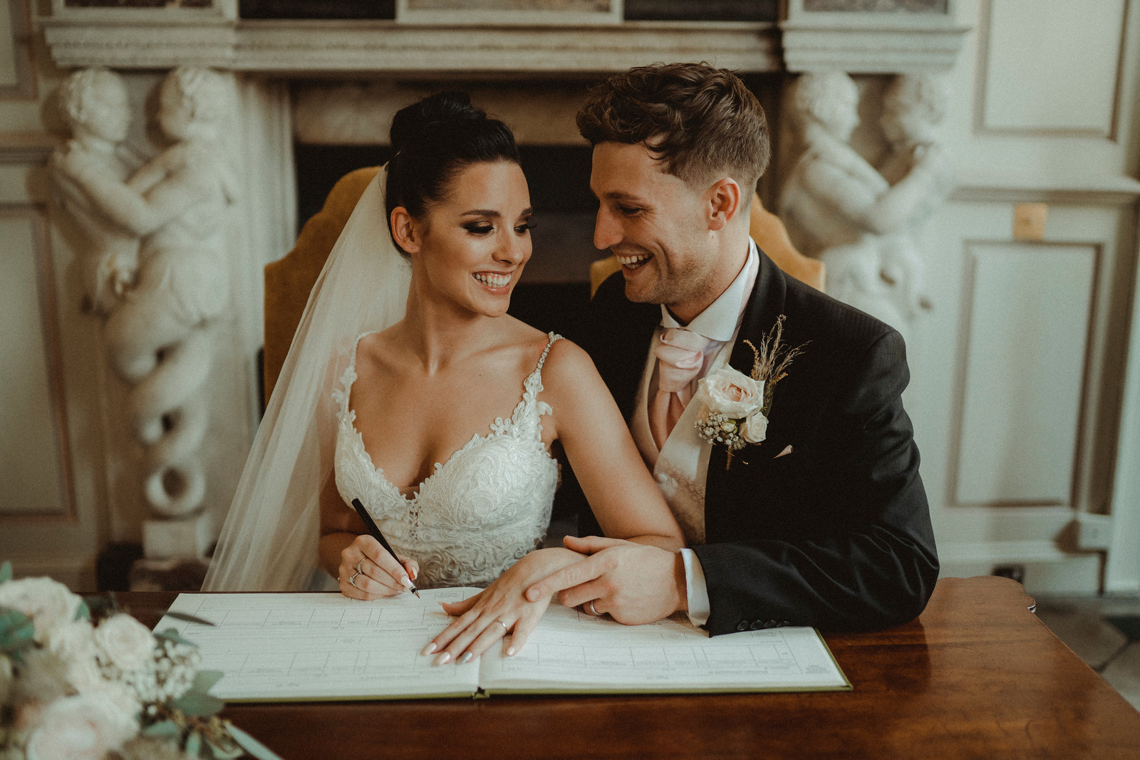 Bride and groom smile at each other as they sign the book