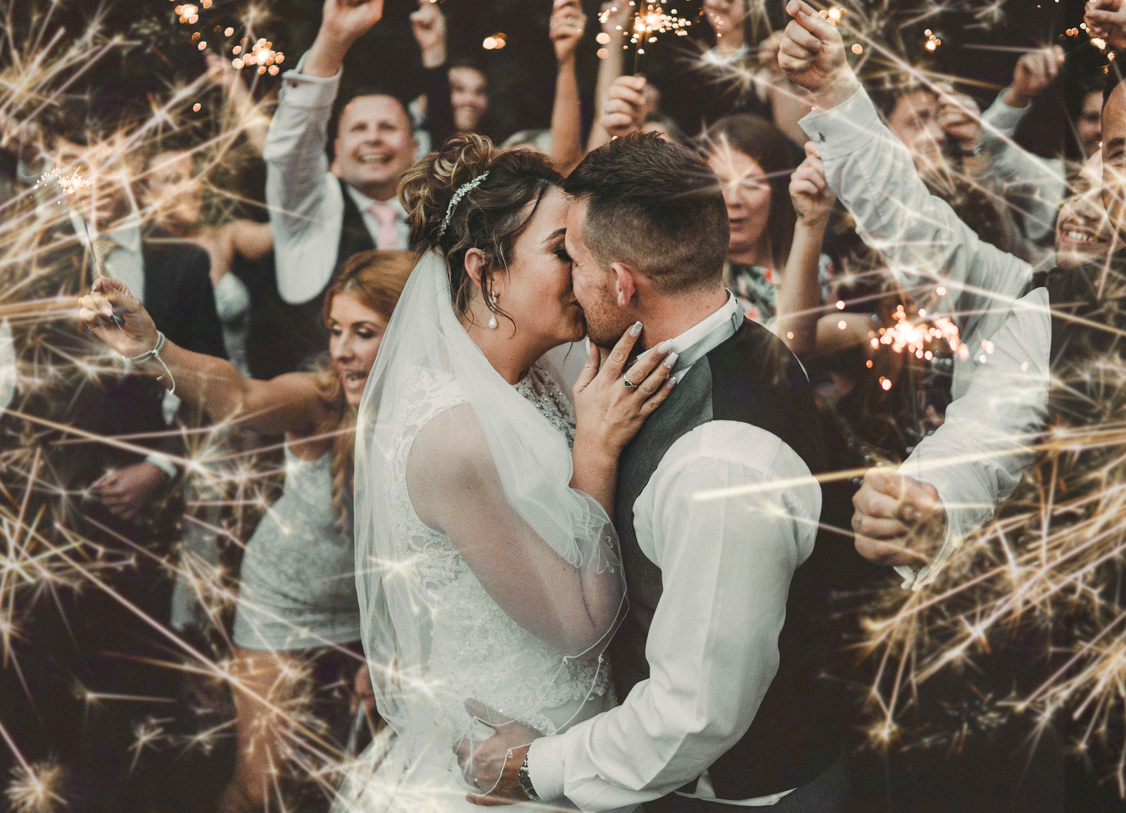 Bride and groom kiss as family and friends wave sparklers around them - Wedding Photographers Bedfordshire