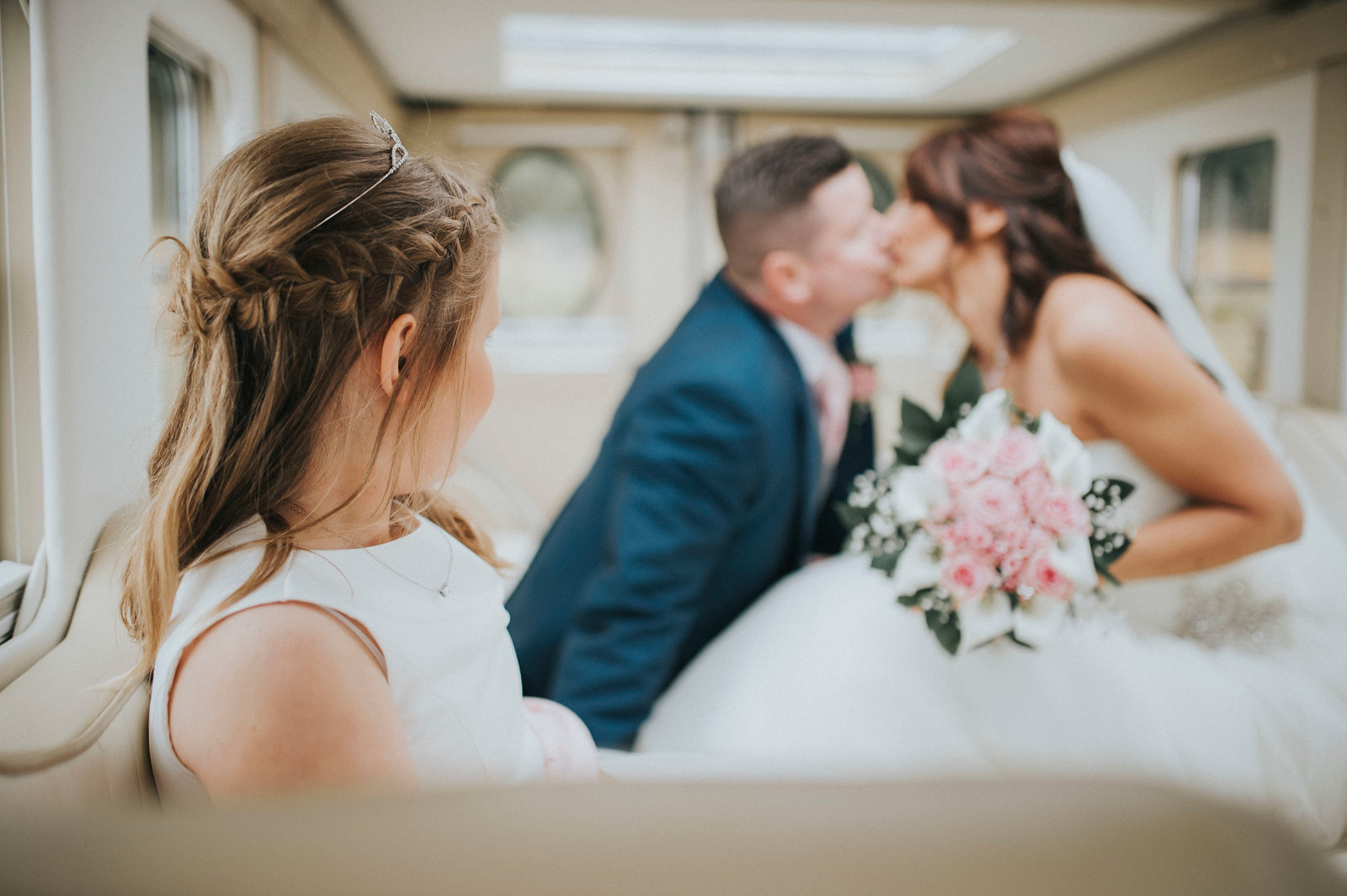 Bride and groom kiss with their daughter behind them - Wedding Photographer South Wales