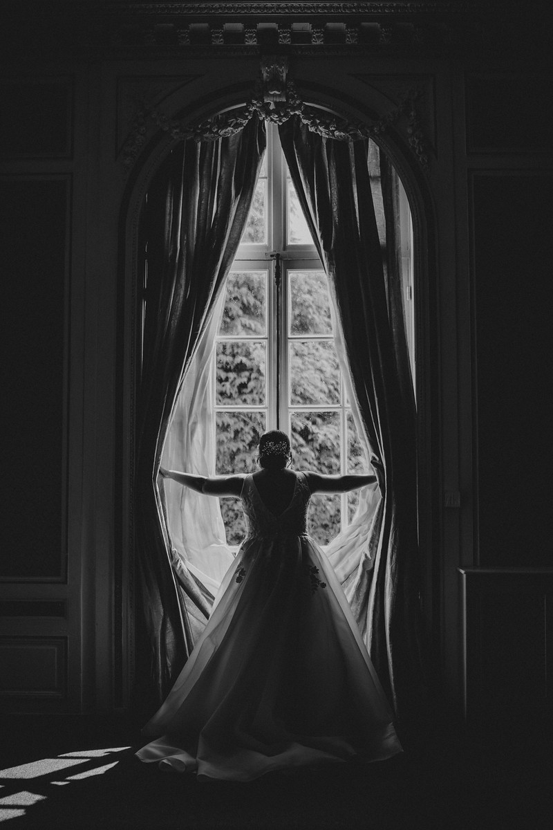Brides stands in the window holding the curtains open
