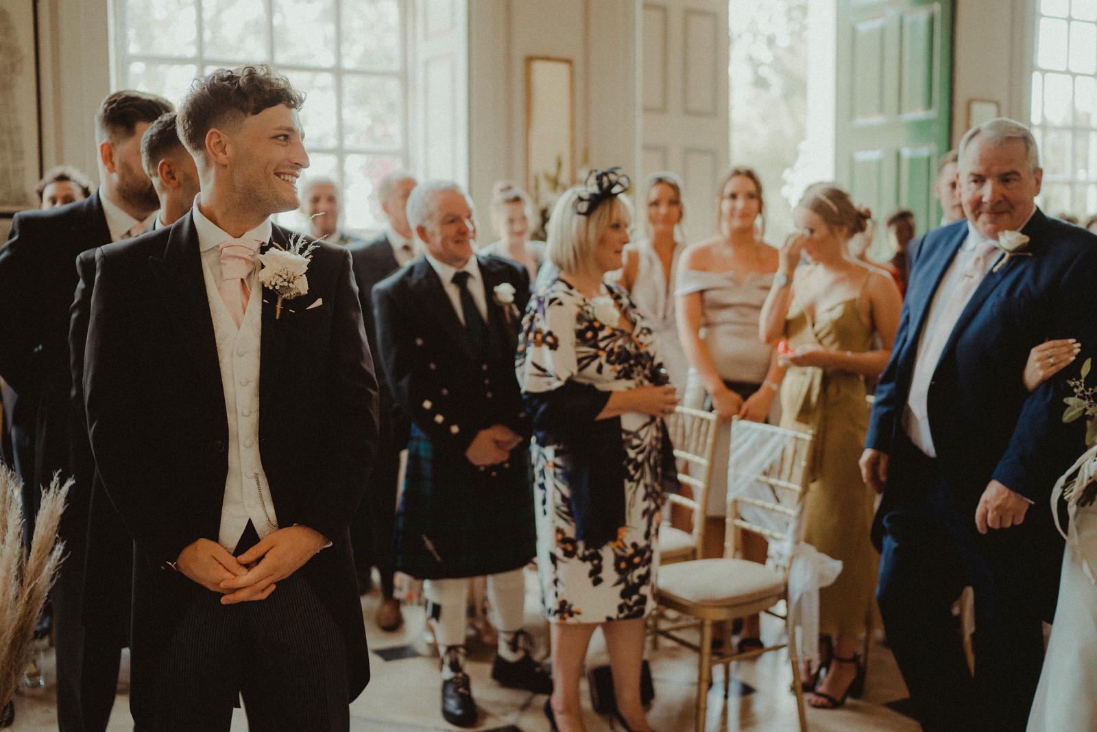 Groom smiles as his bride walks down the aisle