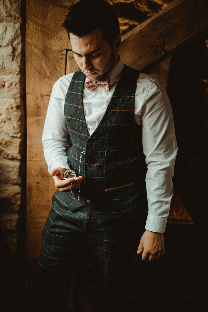 Groom looking at his pocket watch, a gift from the bride