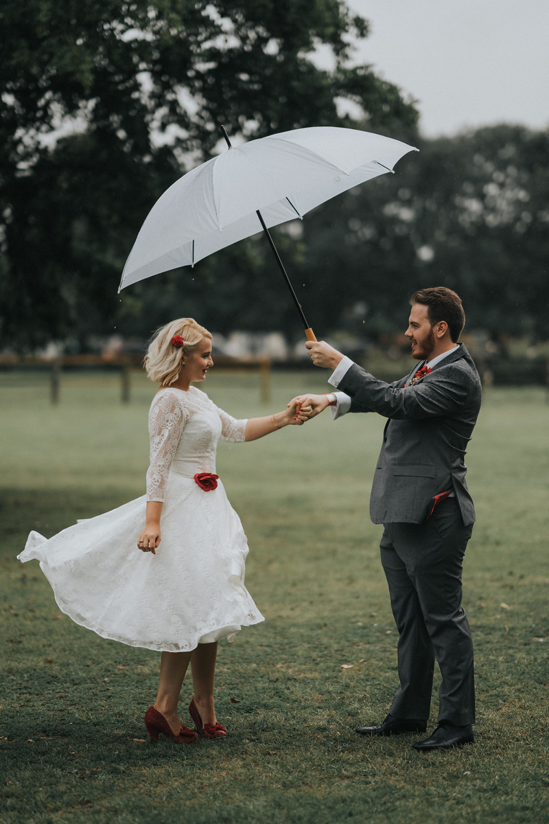 Bride and groom in the middle of their outside venue, as rain falls over them