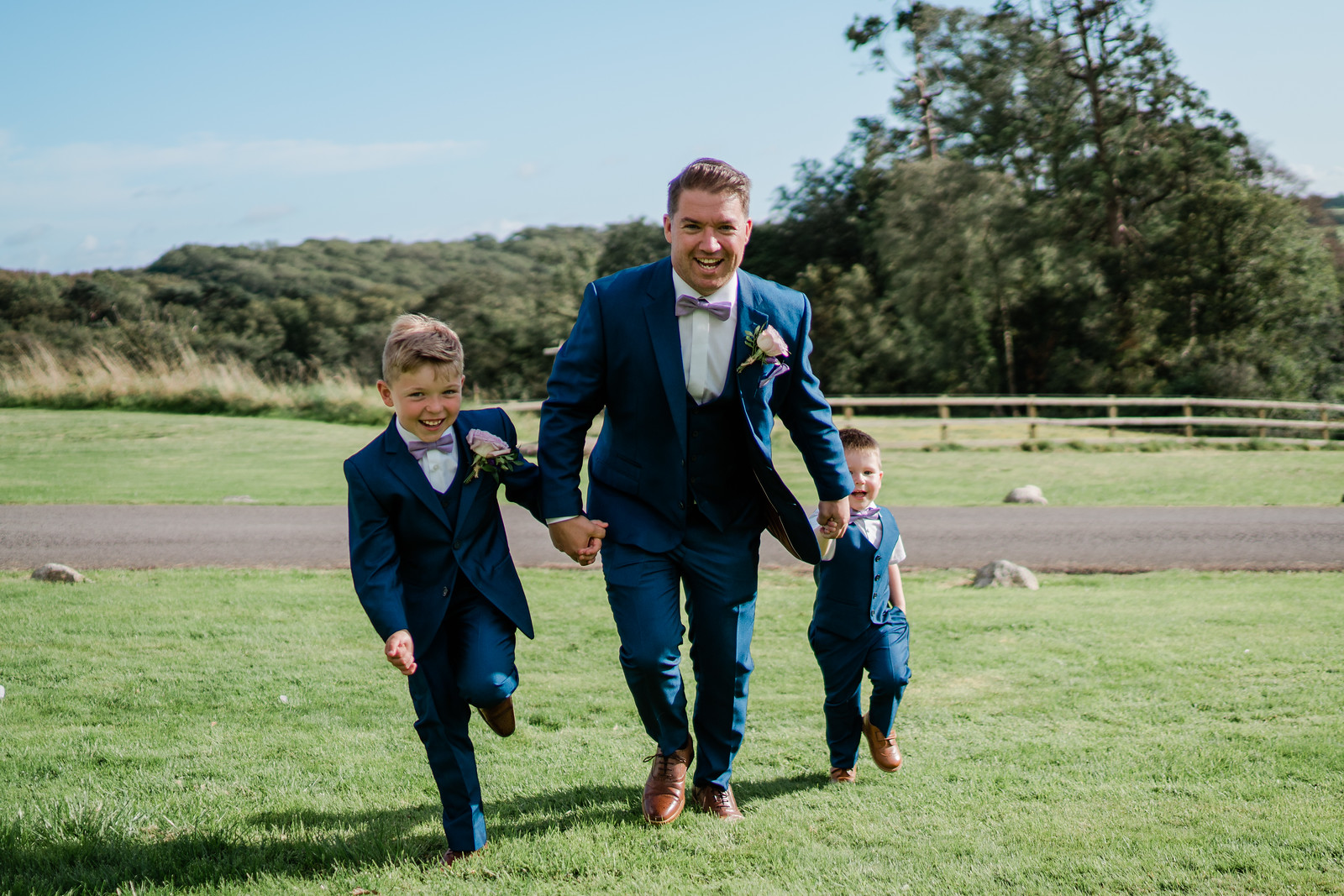 Groom and his sons run through the gardens of the venue