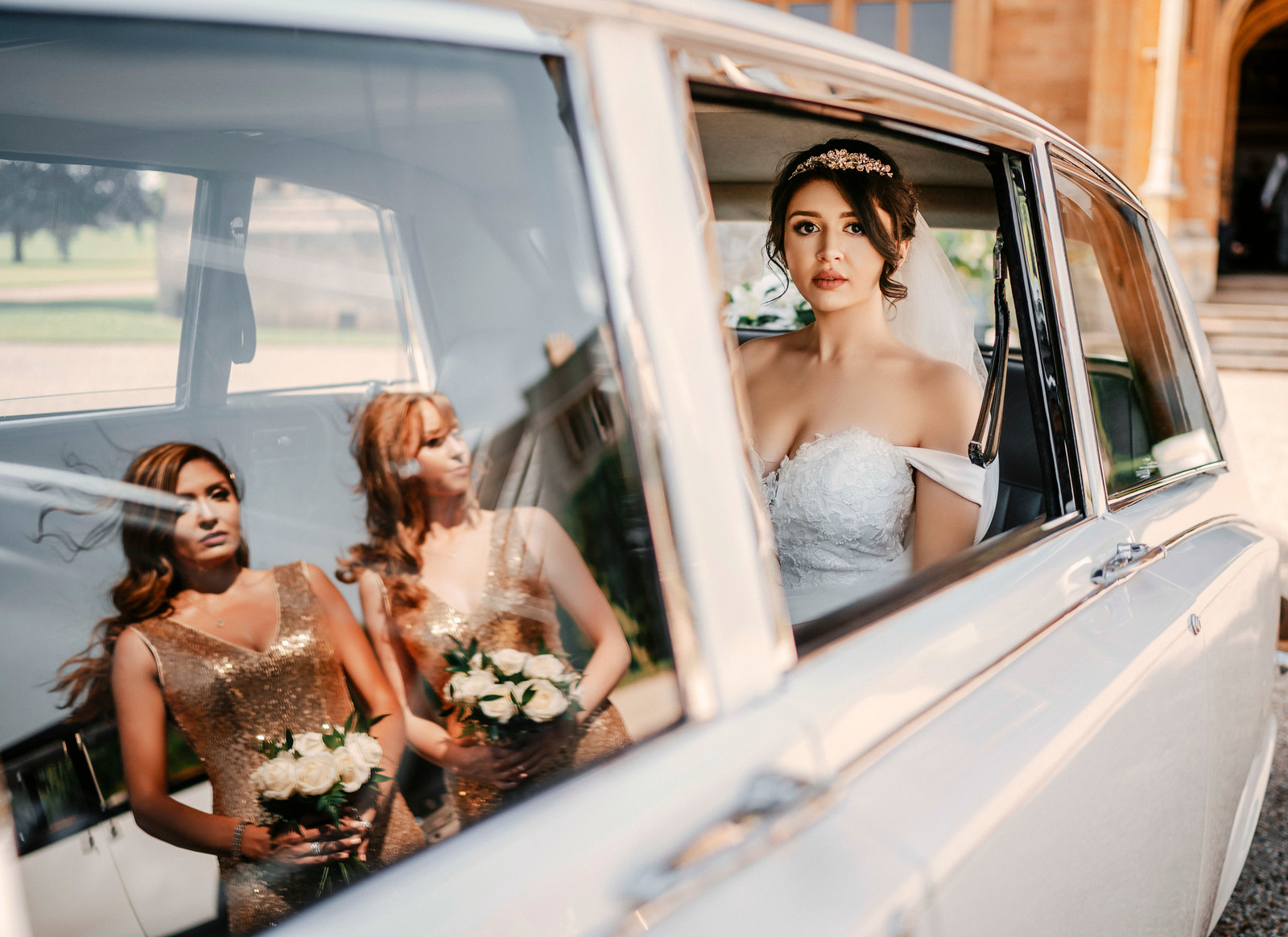 Bride is sat in the wedding car, looking out of the window, with the reflection of her bridesmaids in the car window - Wedding Photography South Wales