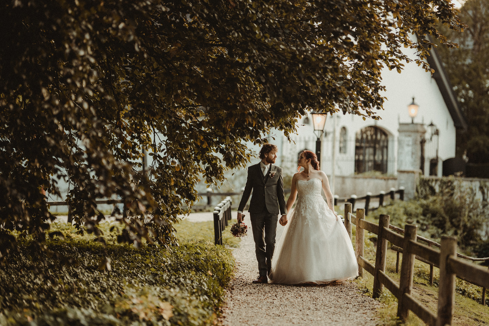 Bride and groom walk through the scenery of their wedding venue - Wedding photographer South Wales