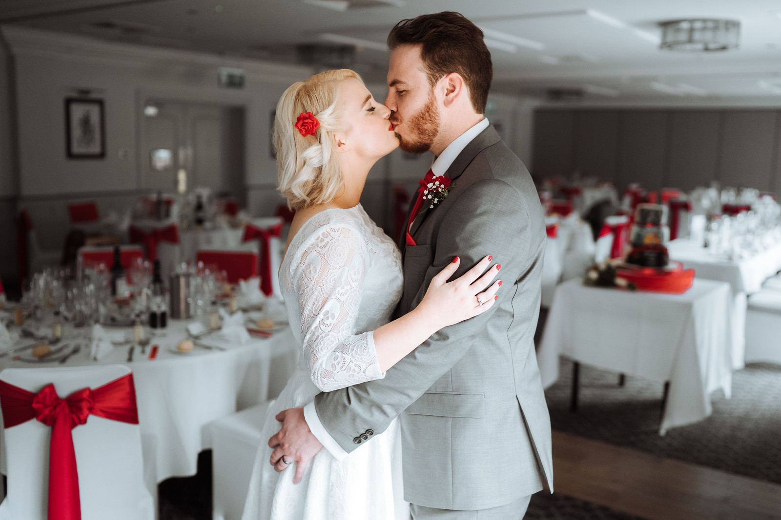 Bride and groom kiss with their reception in the background