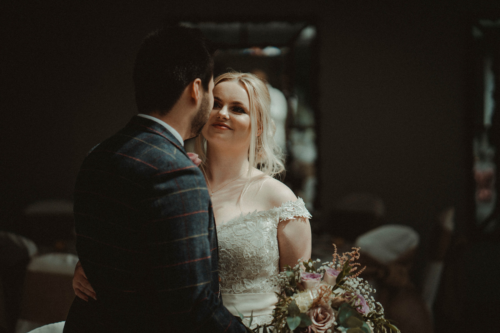 Bride smiles as she looks into the grooms eyes