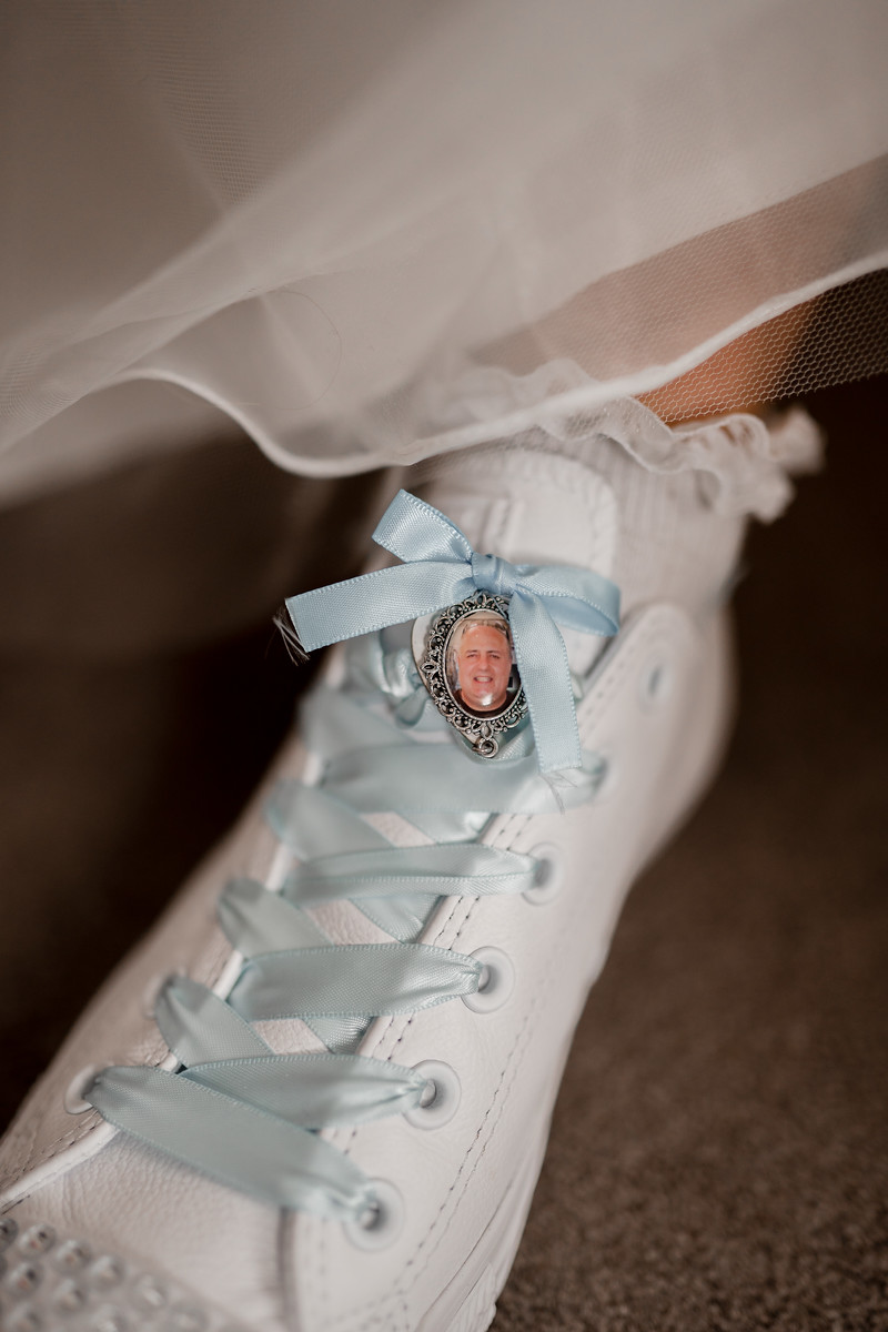 Brides converse wedding shoes with a picture of her dad tied in the blue laces
