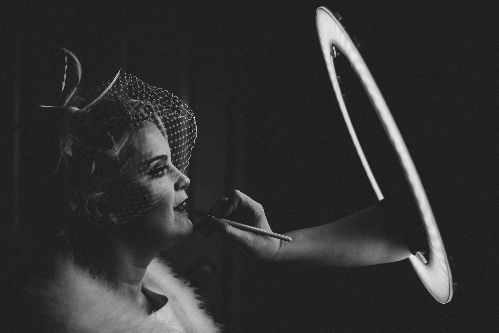 Creative and unique wedding photo of bride having her make-up done