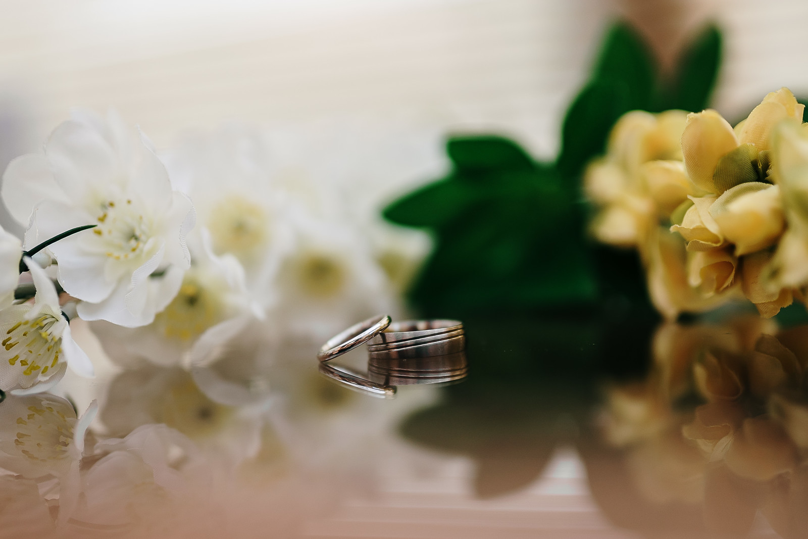 Wedding rings with flowers in the background