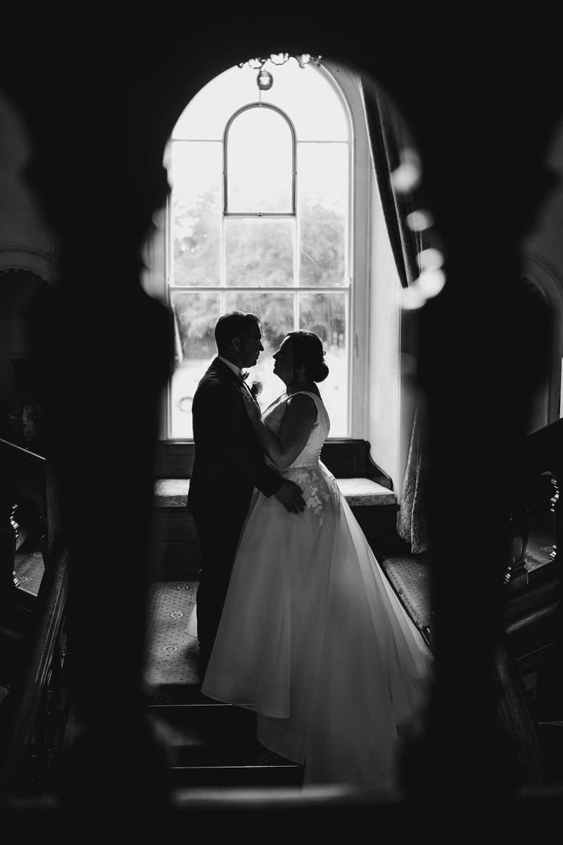 Bride and groom stand together as their photo is taken through a gab in the staircase