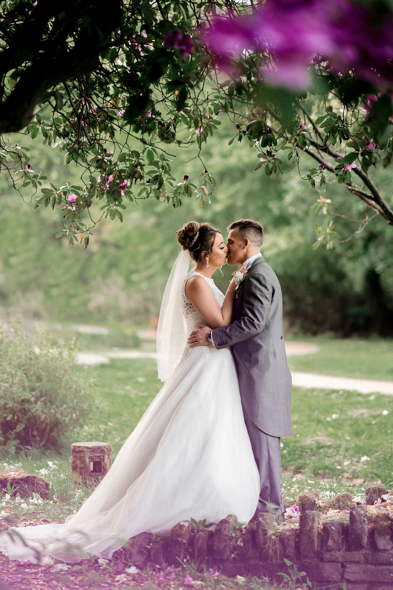Bride and groom kiss, surrounded by flowers