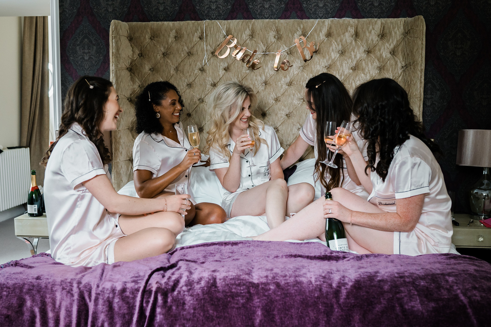 Bride and bridesmaids having a drink before getting ready