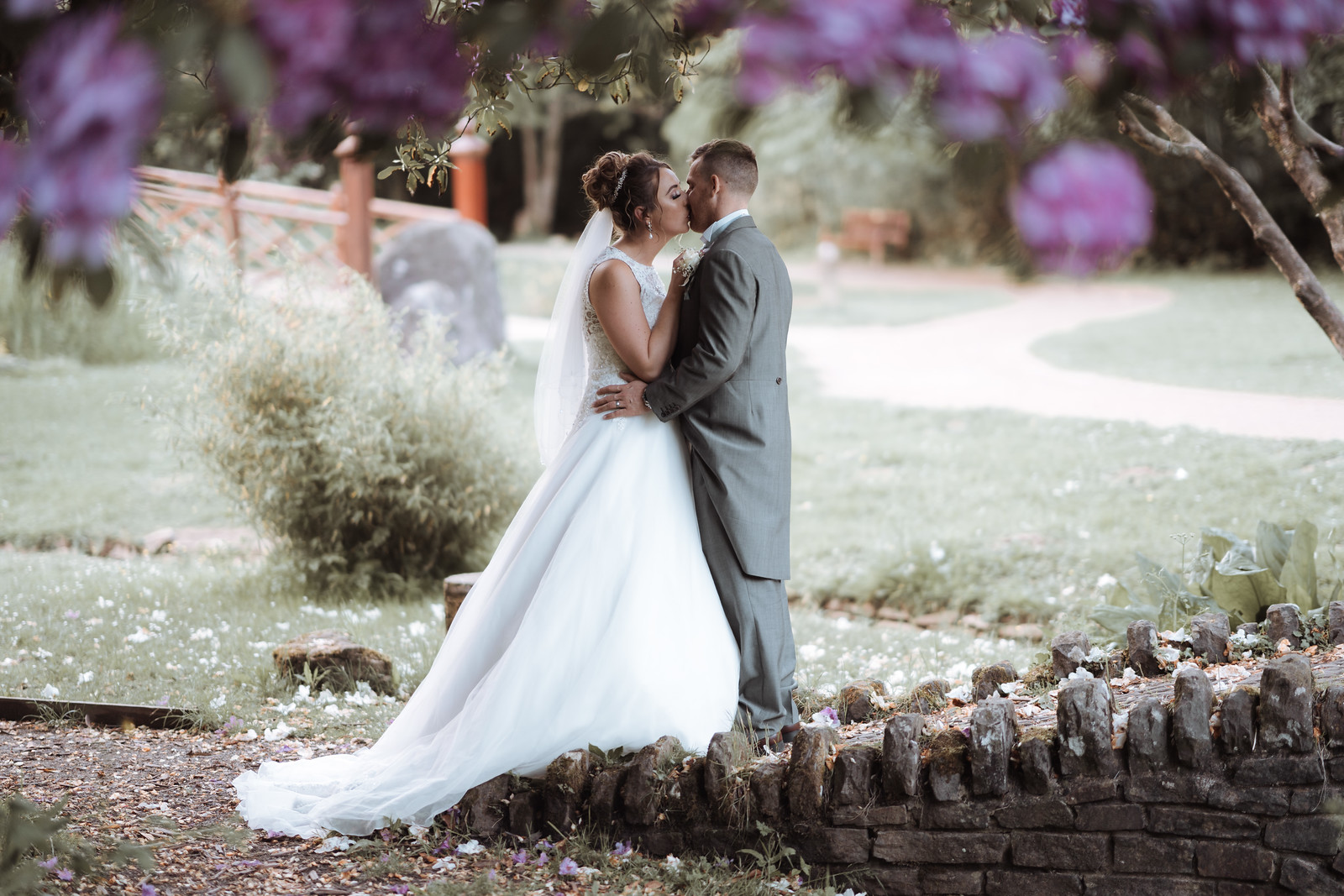 Bride and groom kiss surrounded by beauty of the gardens