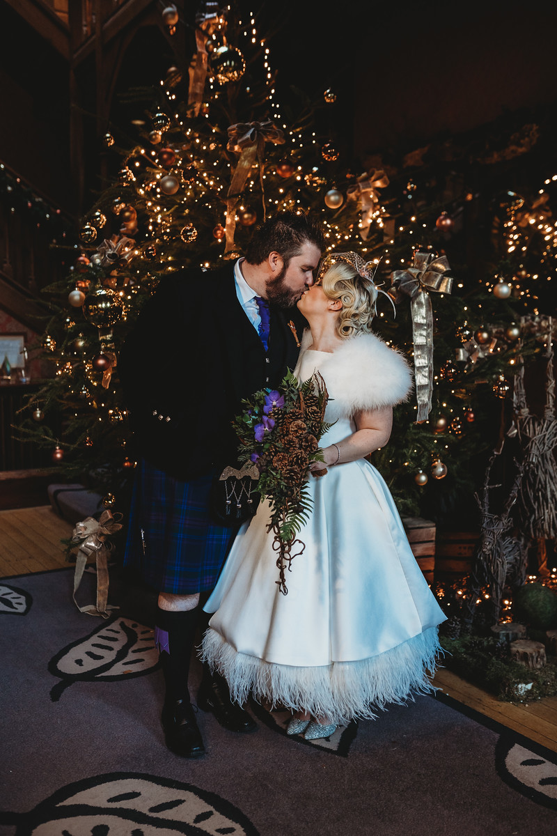 Bride and groom kiss wedding photo with a Christmas tree background
