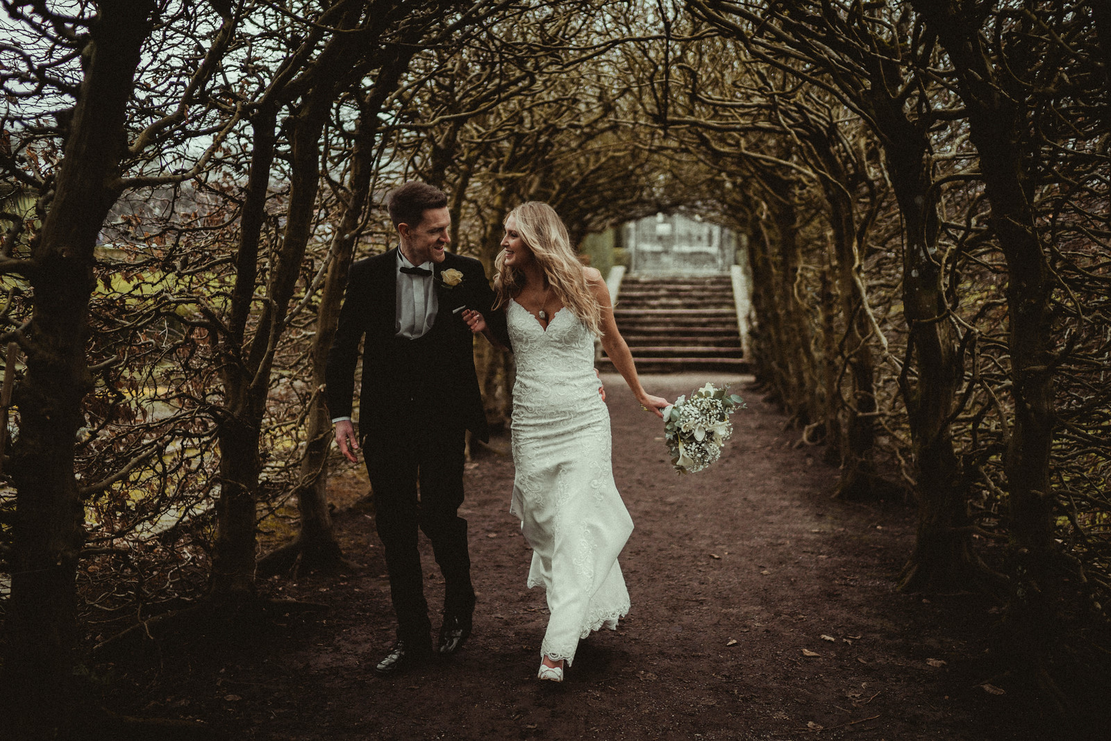 Bride and groom walk through a woodland archway - South Wales Wedding Photographers