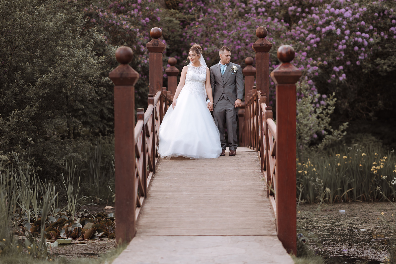 Bride and groom walk across the bridge in the beauty of the outside of the venue