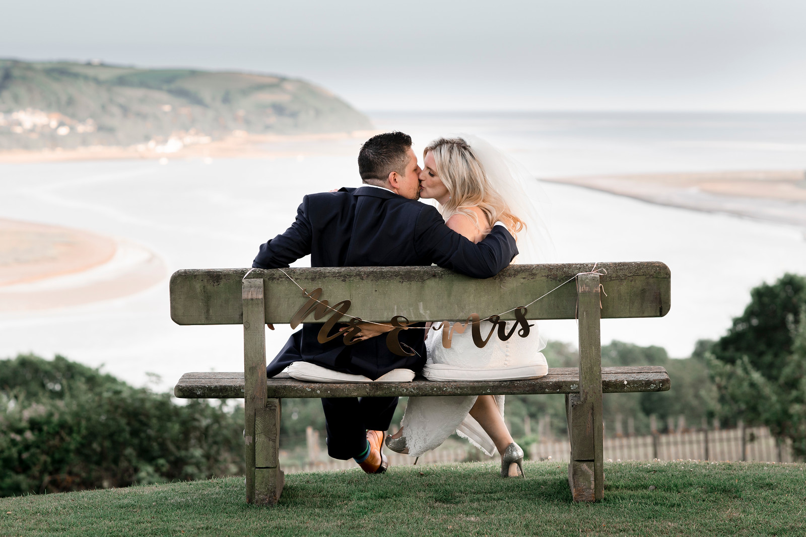 Bride and groom kiss as they overlook a stunning view