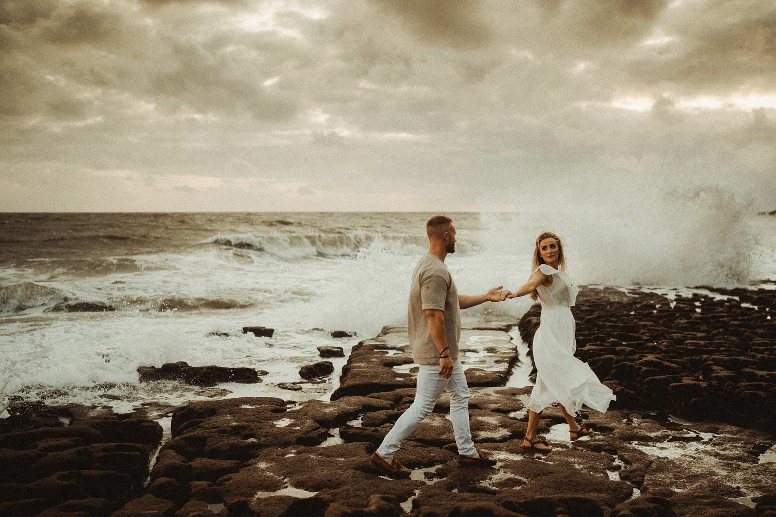 Couple walk across the beach holding hands