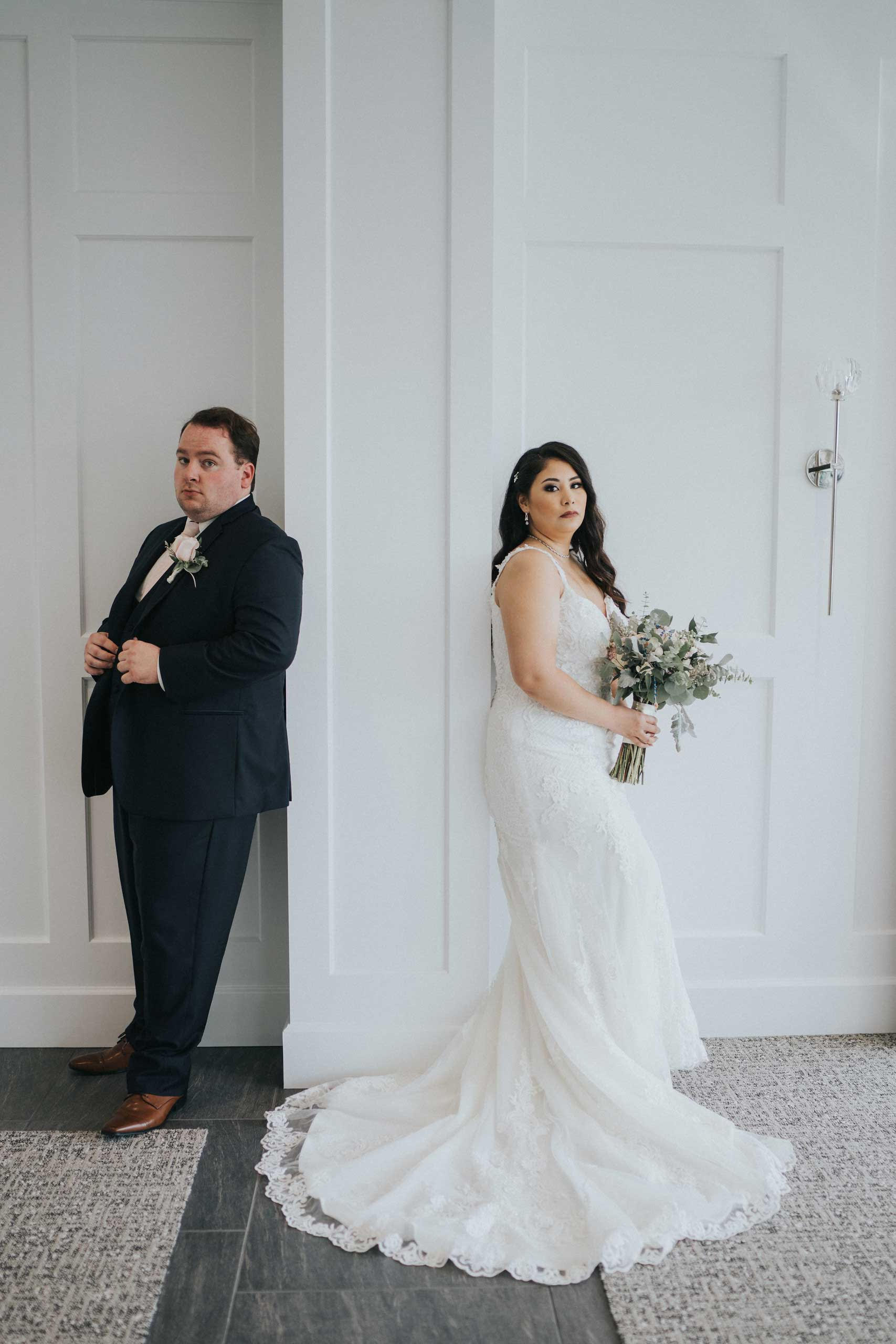 Bride and groom stand back onto a wall