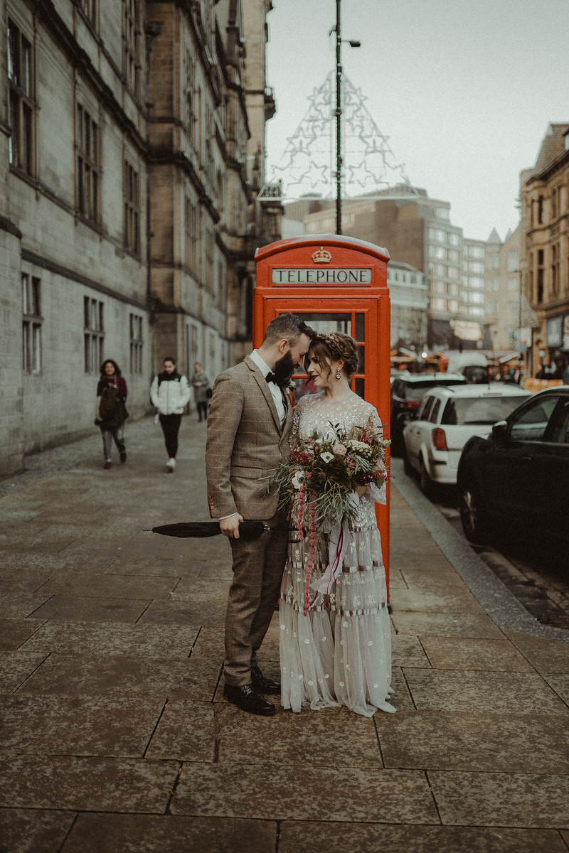 Bride and groom smile at each other, with a telephone box behind them