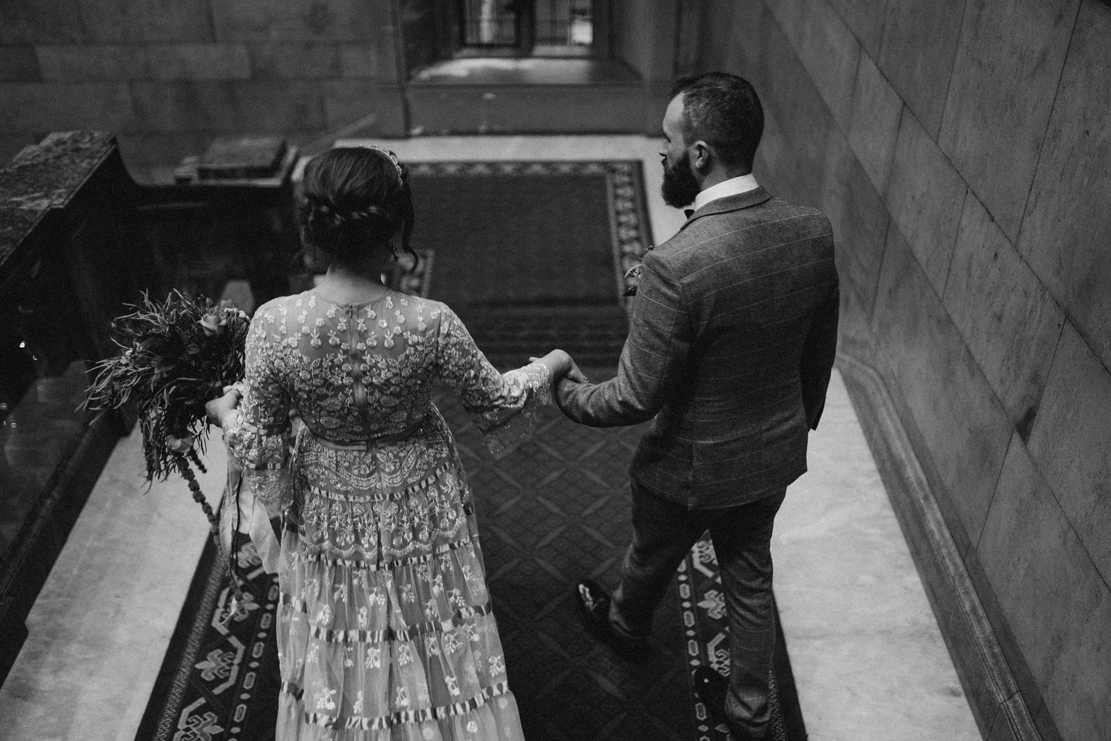 Bride and groom walk down the grand stairs, holding hands