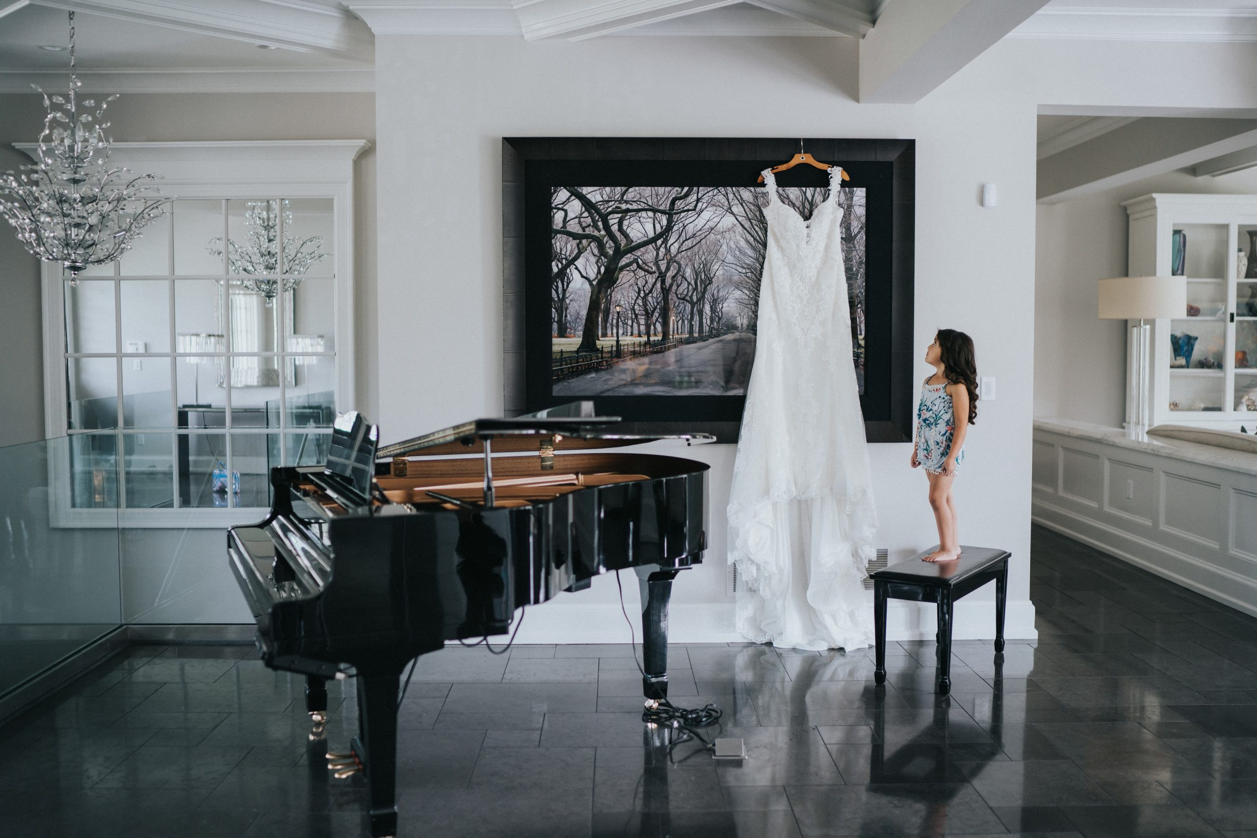 Child looks up to the brides wedding dress