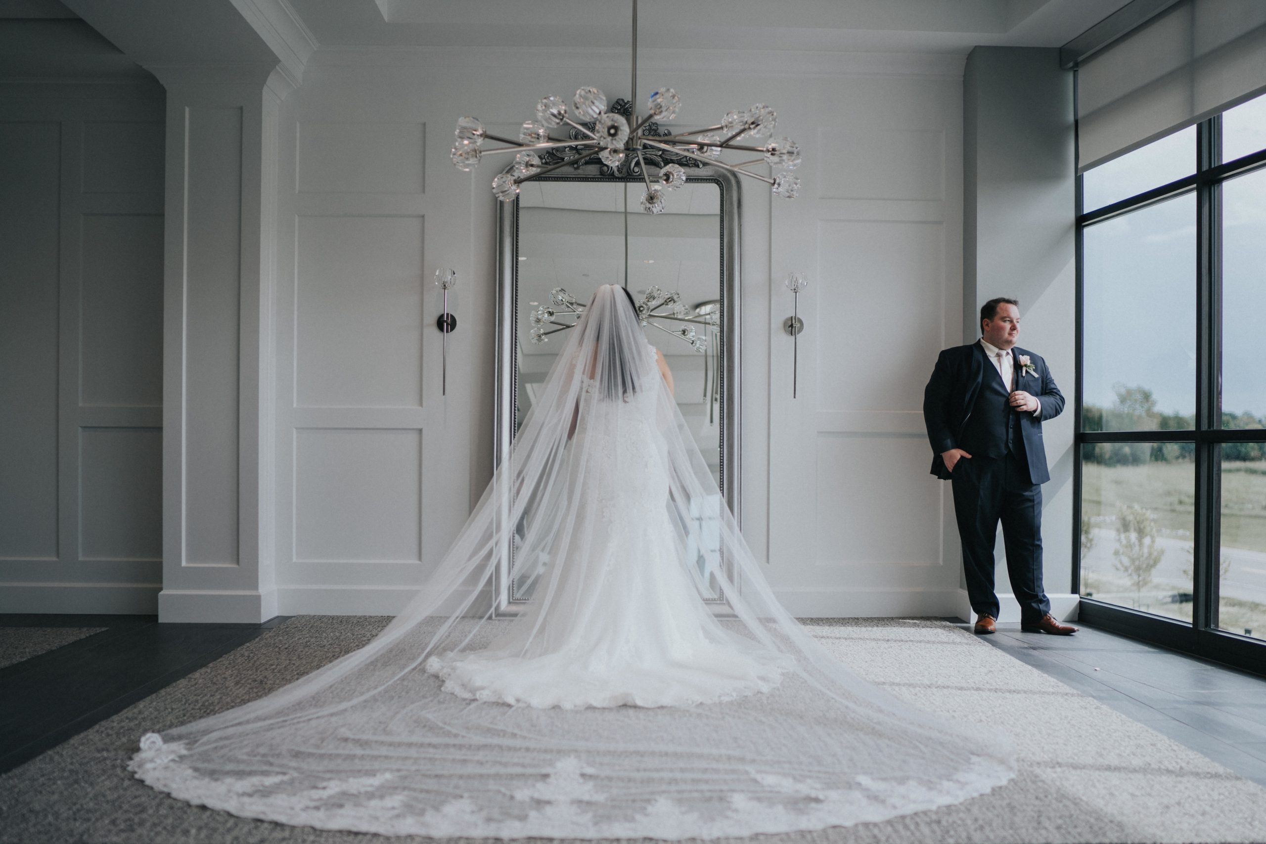 Bride faces the mirror with her dress on