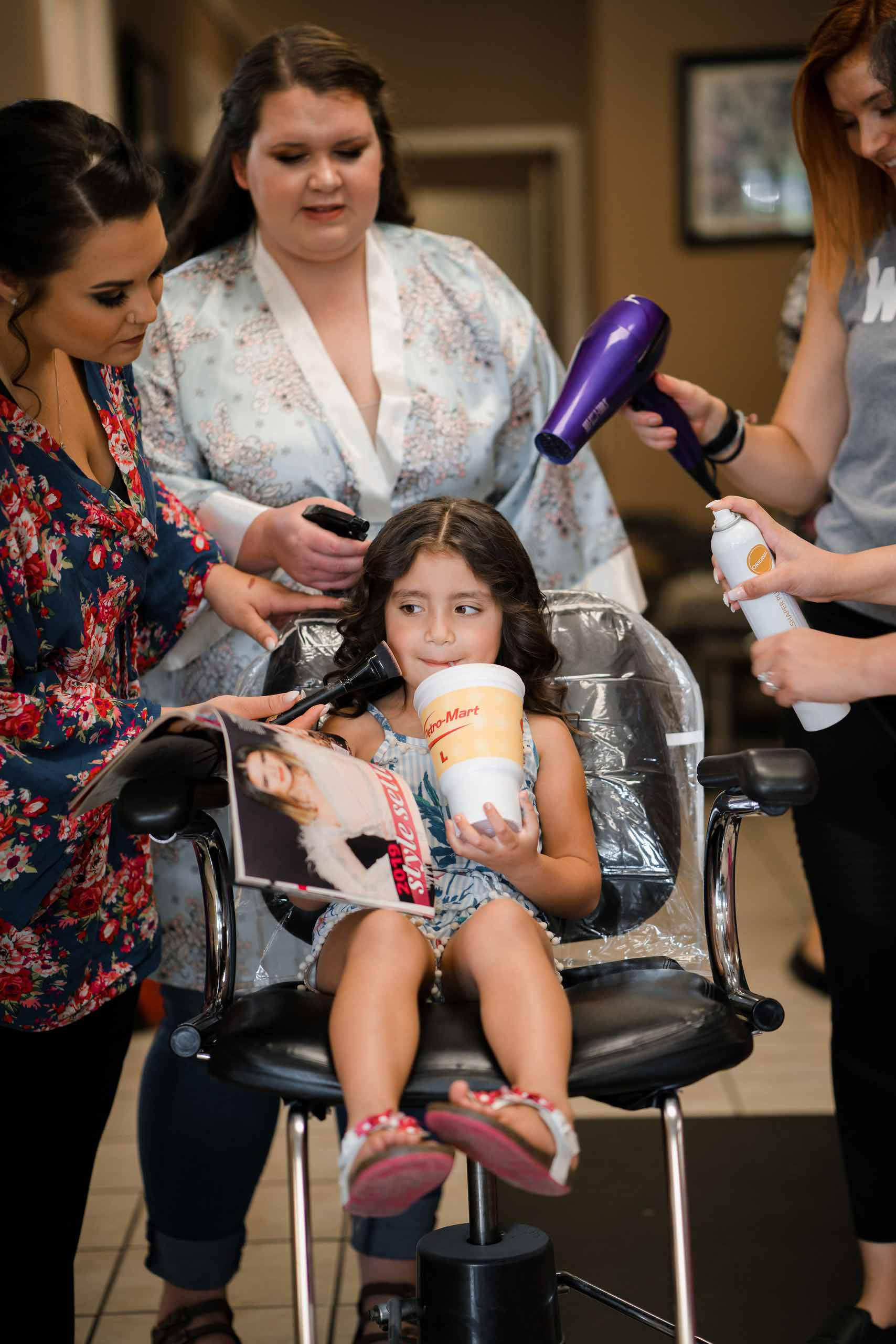 Young child sat in a chair, as the bridesmaids is doing her hair