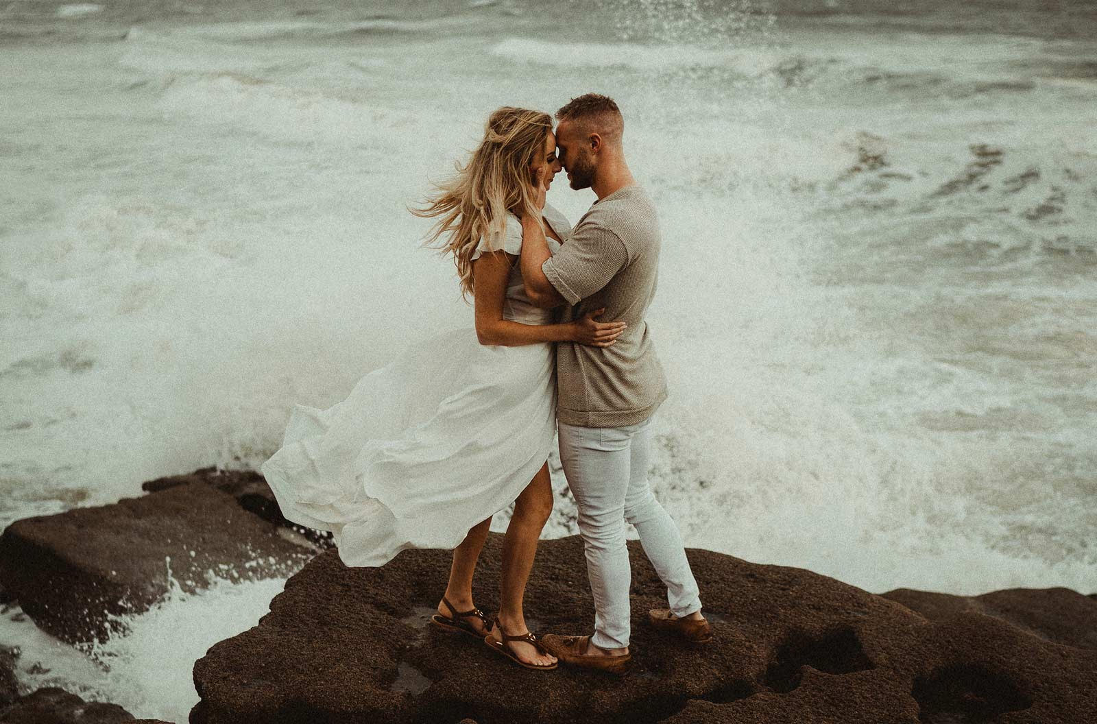 A couple stands on a rock as the sea surrounds them.