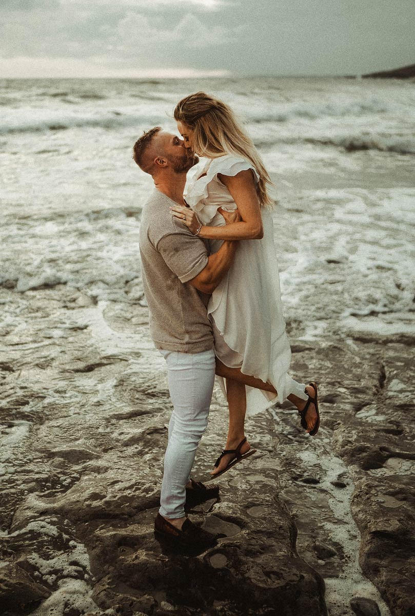 Man picks up his partner as the sea surrounds them
